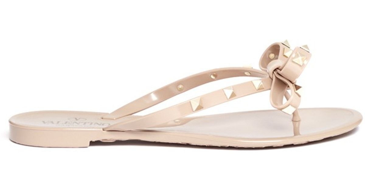 057690a33aef5 Lyst - Valentino Rockstud Bow Flat Jelly Sandals in Natural