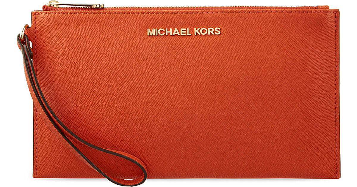 8c7e7cd14b39 MICHAEL Michael Kors Leather Travel Clutch Bag in Orange - Lyst