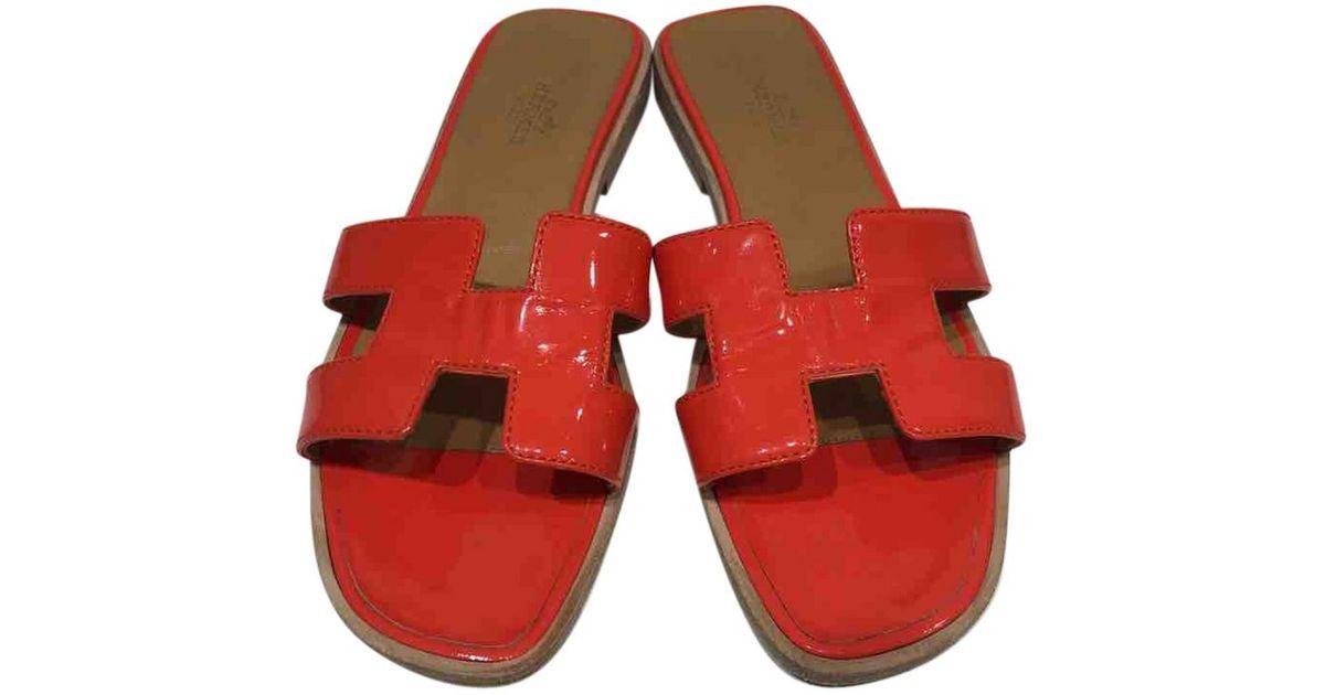 2e429802fc79 Lyst - Hermès Oran Patent Leather Sandals in Orange