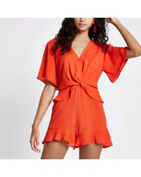 26573a6727b River Island Knot Front Frill Playsuit in Red - Lyst