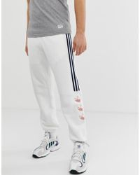adidas Originals Pantalon de jogging à rayures et logo trèfle - Blanc DV3148