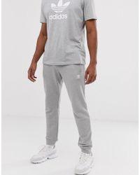 adidas Originals Pantalon de jogging ajusté avec logo brodé - Gris