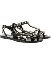 ed5a6bf9af10 Valentino Rockstud Bow Flat Jelly Sandals in Black - Lyst