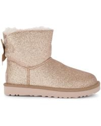 UGG - Mini Bailey Bow Sheepskin And Golden Glitter Ankle Boots Women's Snow Boots In Gold - Lyst