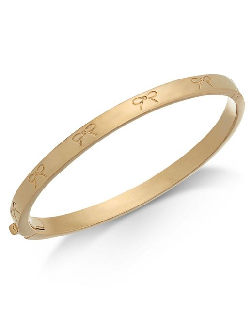 Kate Spade - Metallic Gold-tone Engraved Bow Bangle Bracelet - Lyst