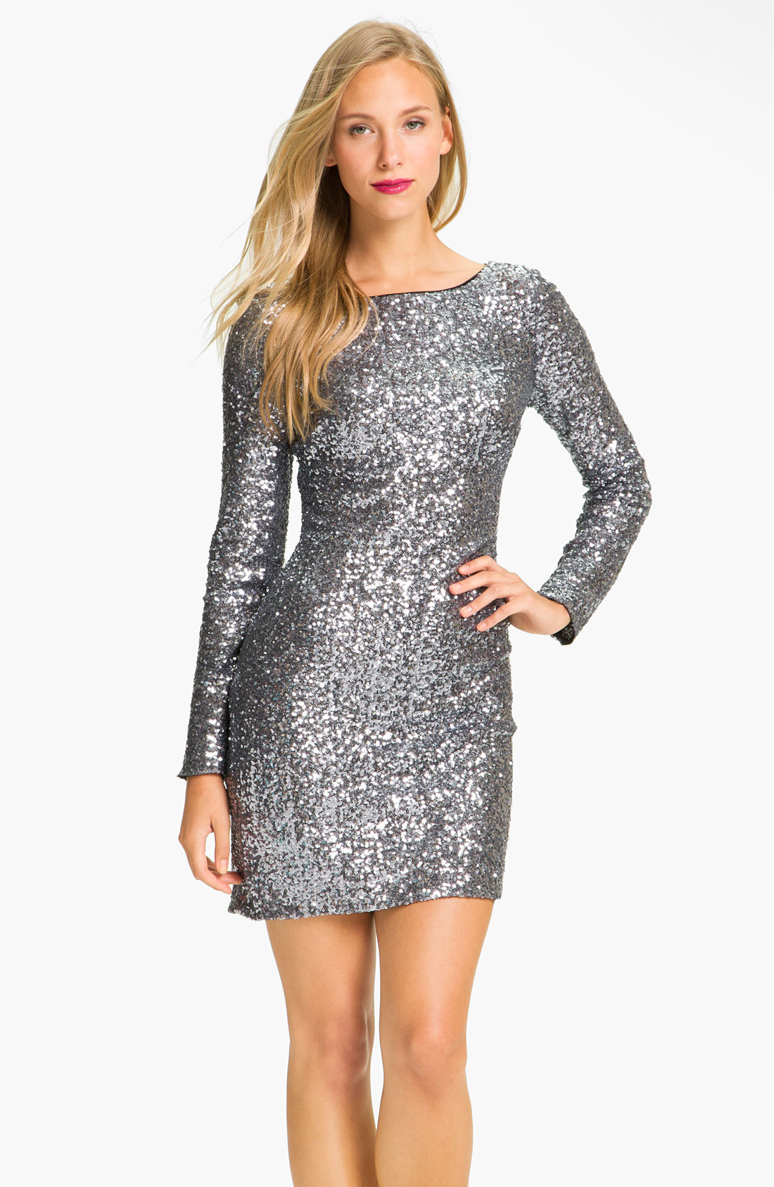 Short fitted nude cocktail dress features long sleeves, cutouts on the shoulders, a deep V neckline, sequin embellishments and a zipper in the back.