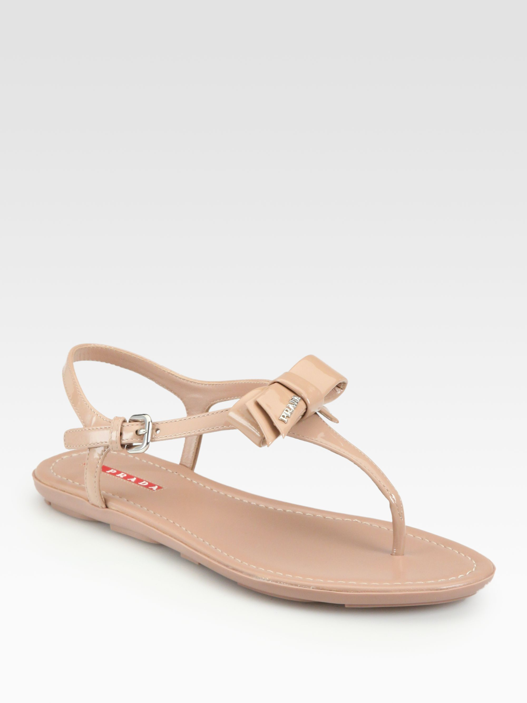 7091efdd783ff9 Lyst - Prada Patent Leather Bow Thong Sandals in Natural