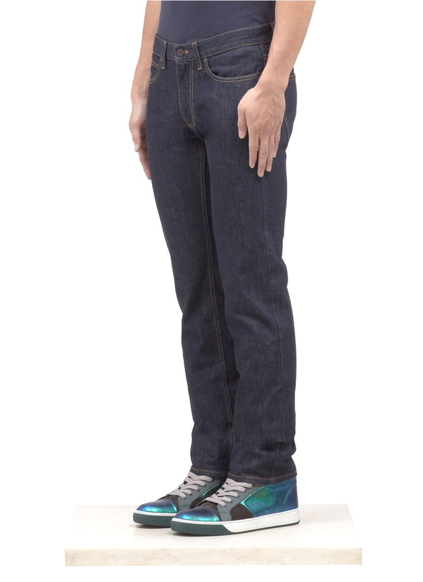 Blue jeans with checkered cuff detail, waist with belt loops, hidden front button placket and patch pockets on the back. A timeless boy's classic, these jeans are easy to wear and create modern stylish lines.