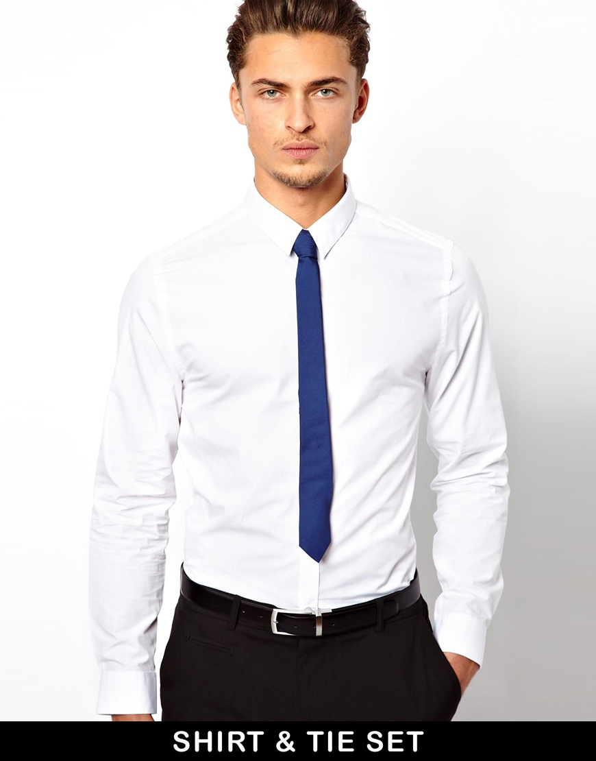 Appearance. The Shirt & Tie is a white button-down long-sleeve shirt with a red-and-blue-striped tie. On the middle of the tie, a squid-like logo clip is seen.