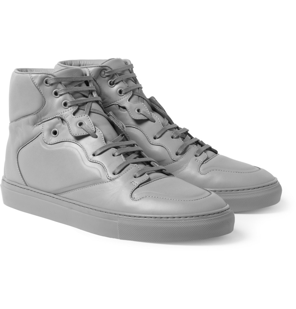 Men's white patent leather Balenciaga round-toe high-top sneakers with PVC side panels, translucent rubber soles and lace-tie closures.