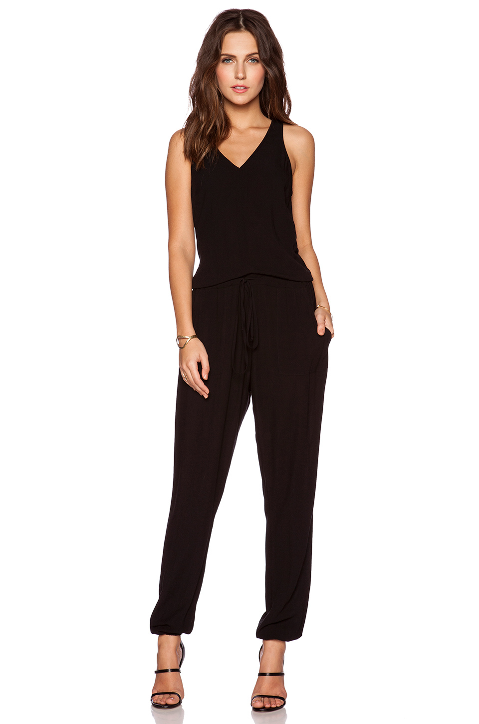 V-neck jumpsuit in woven fabric with a printed pattern. Wrapover front with concealed snap fastener at top, 3/4-length sleeves with cuffs, and an elasticized seam at waist with removable tie belt.
