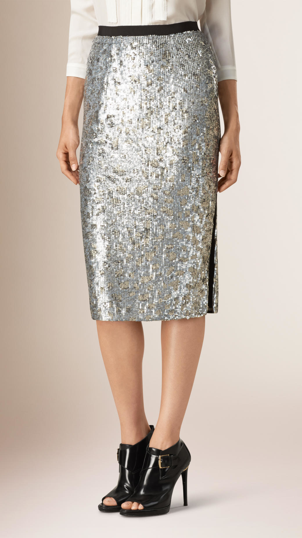 Shine all night in our Glitter Girl skirt! This style features a beautiful mesh overlay with mini sequin glitter throughout. This skirt sits high on the waist and has a notched split .