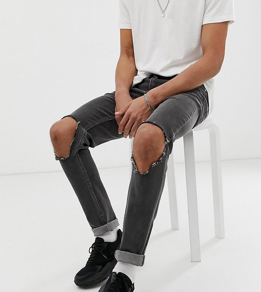 b56dc6ba8c2 ASOS. Vaqueros ajustados en negro desgastado con roturas abiertas en las  rodillas de Tall de hombre