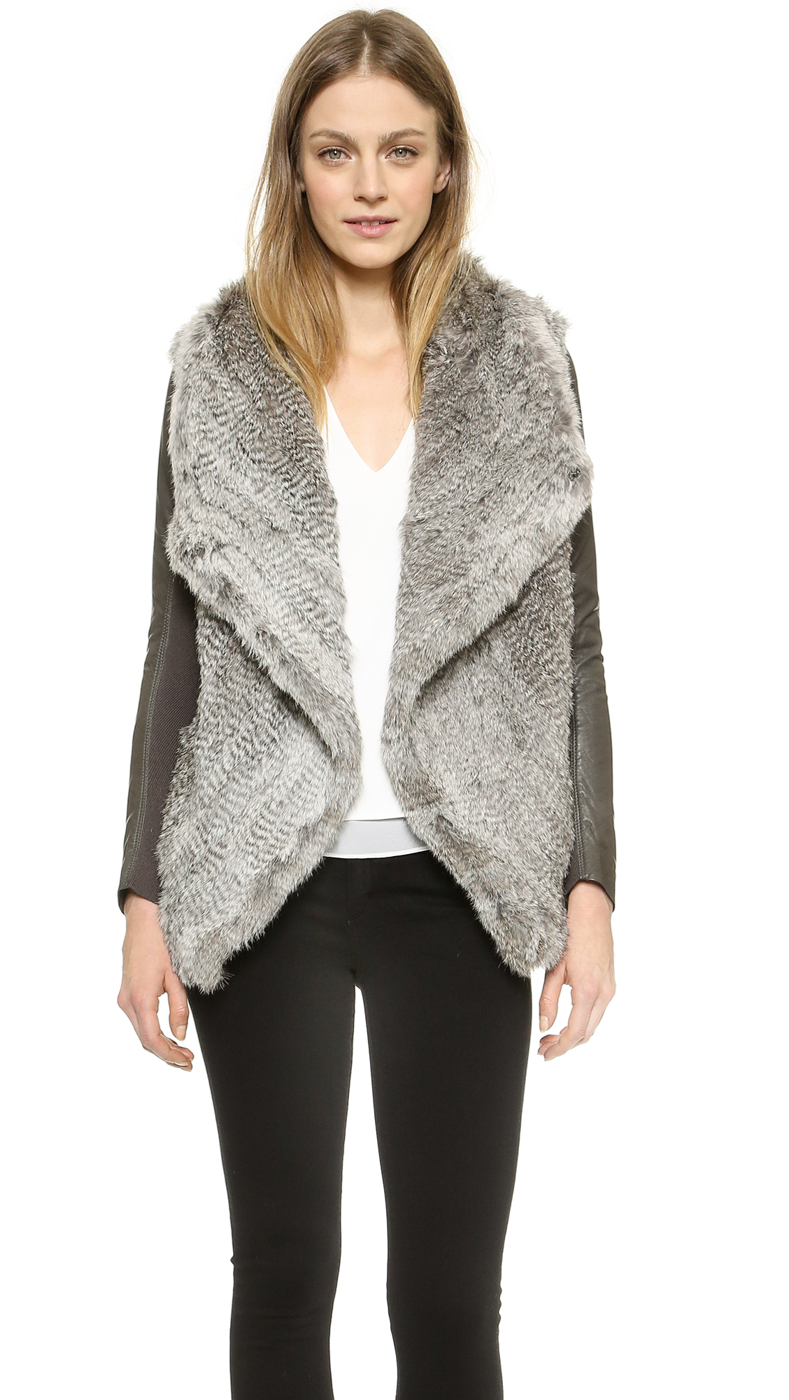 """Our Black Fur Jacket with leather sleeves """"Vogue"""" turns every winter outfit into a real eye-catcher. The combination of super fluffy fox fur and slim leather sleeves guarantees that this jacket feels incredibly comfortable to wear. Not only can you wear this jacket as an exquisite winter jacket, but also a glamorous fur vest."""