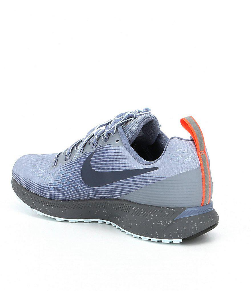 2ad1f6a77d7 ... wholesale lyst nike women s air zoom pegasus 34 shield running shoes in  blue 0b296 8f009