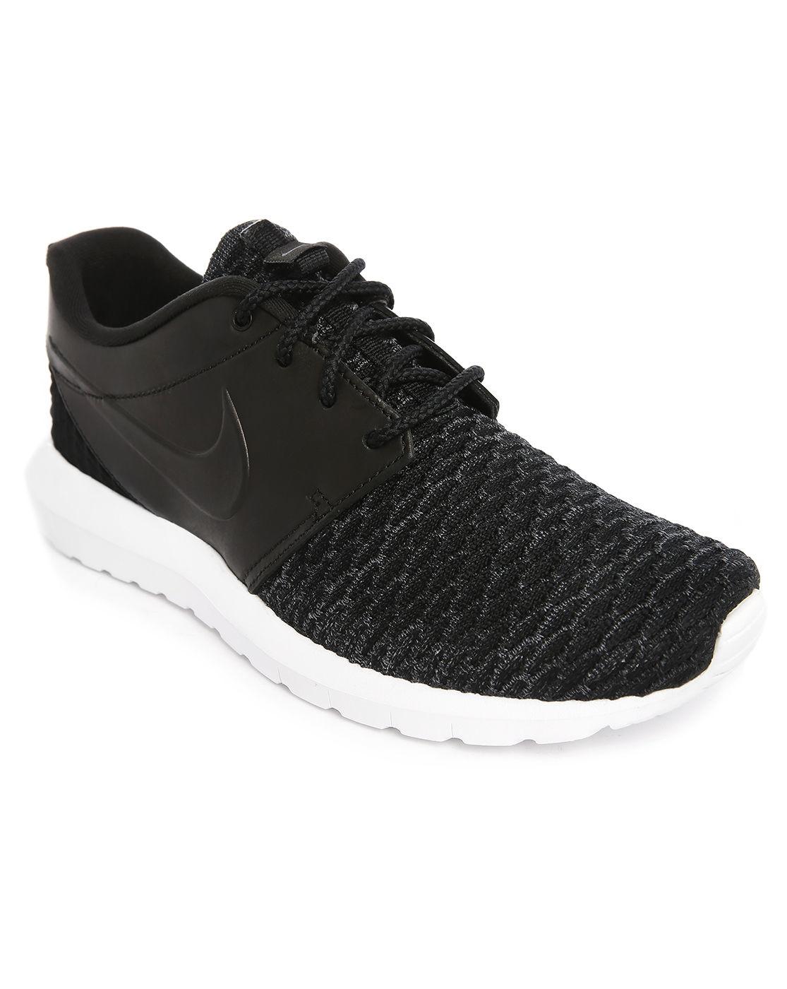 nike roshe run flyknit black sneakers in black for lyst