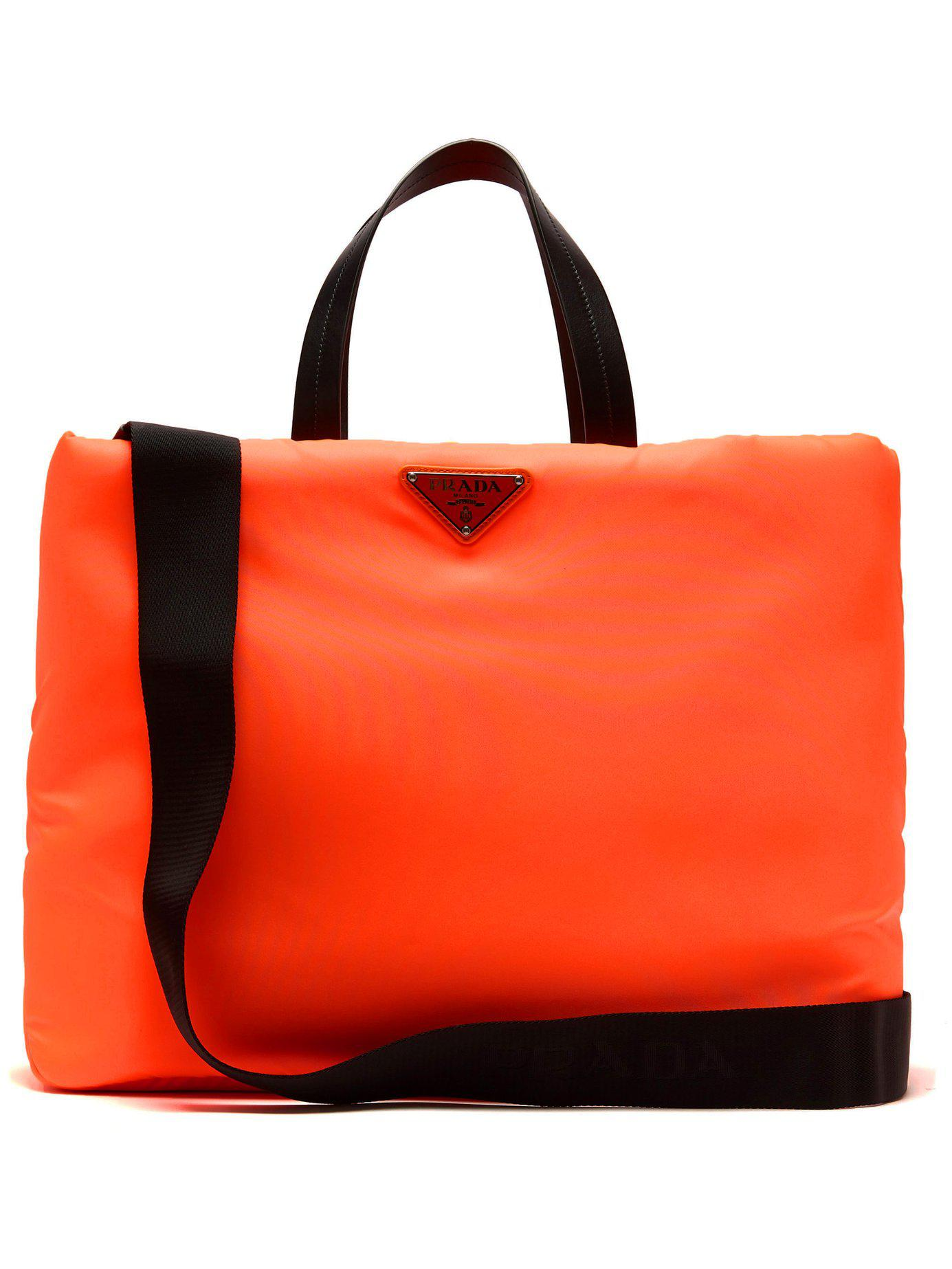 4a10aa06ec2 10fdaa0b43e9 Prada Logo Embellished Padded Nylon Tote Bag in Orange - Lyst  ...