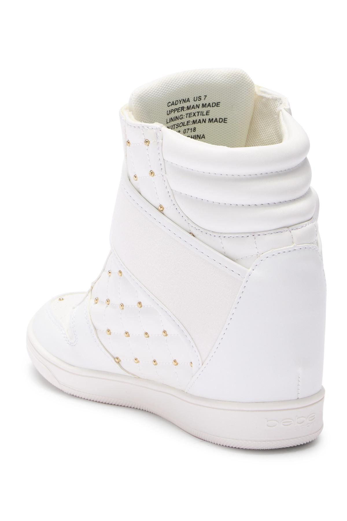 3bc08b536bd7 Lyst - Bebe Studded Hi-top Wedge Sneaker in White